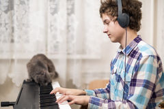 Boy plays piano. A shot of teenager boy playing piano Royalty Free Stock Images
