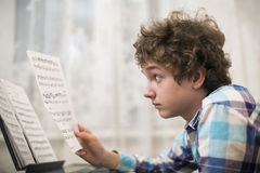 Boy plays piano Royalty Free Stock Photo