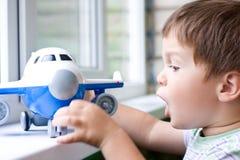 Boy plays with plane Stock Photo