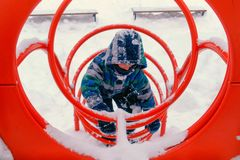 Boy plays on playground in tonnel in winter. stock photography