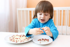 Boy plays with rice and shell beans Royalty Free Stock Photos