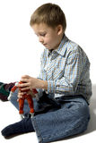 The boy plays with the robot. The little boy in a blue shirt plays with the robot Stock Image