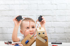 boy plays with the robot and servo royalty free stock images