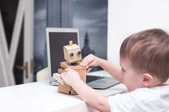 Boy plays with the robot  on a white table at home. Boy plays with the robot at  home Royalty Free Stock Image