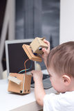 Boy plays with the robot  on a white table home Stock Photos