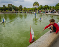 Boy plays with a sailboat at the pond at Luxembourg Gardens Stock Photo