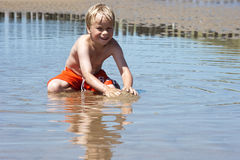 Boy plays with sand Stock Photo