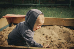 A boy plays in the sand in the sandbox. And very happy Royalty Free Stock Photography