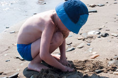The boy plays sand on seacoast Stock Photography