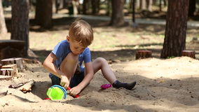 A boy plays in the sandbox. With shovel and pail and shapes for sand stock video