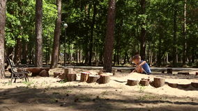A boy plays in the sandbox. With shovel and pail and shapes for sand in a pine forest stock video