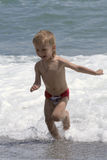 Boy plays at the seaside Stock Images