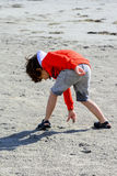 Boy plays at the seaside. In the wind Royalty Free Stock Photo