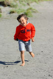 Boy plays at the seaside. In the wind Stock Image