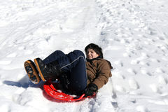 Boy plays with sledding on snow Royalty Free Stock Image