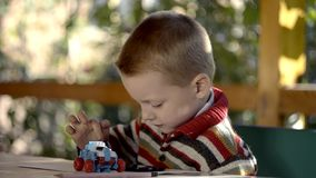 A boy plays on a smart phone outdoor stock footage