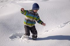 A boy plays in the snow. A boy plays in the snow in the mountains in winter royalty free stock images
