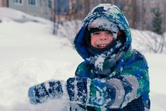Boy plays in snow, looks at camera and smiling. royalty free stock photos