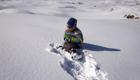 A boy plays in the snow. A boy plays in the snow in the mountains in winter royalty free stock photography