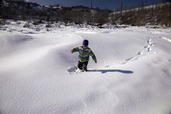 A boy plays in the snow. A boy plays in the snow in the mountains in winter stock photo