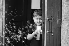 A boy plays with soap bubbles. In the yard Royalty Free Stock Images