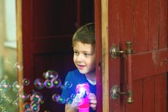A boy plays with soap bubbles. In the yard Stock Photo