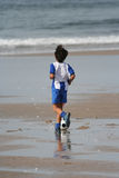 Boy plays soccer. In the beach Royalty Free Stock Images