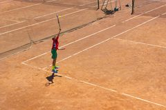 The boy plays tennis on the orange dirt court. Court hard. Boy playing tennis on a dross court, The boy plays tennis on the orange dirt court. Court hard. Young royalty free stock photography