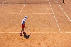 The boy plays tennis on the orange dirt court. Court hard. Boy playing tennis on a dross court, The boy plays tennis on the orange dirt court. Court hard. Young royalty free stock images