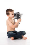 Boy plays to shoot at the old camera Royalty Free Stock Photo