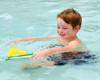 Boy plays with toy boat while cooling off in pool Royalty Free Stock Photo