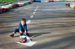 Boy plays with a toy car. Four year old boy sits on the road and plays with the toy car. Season - spring Royalty Free Stock Image