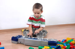 Boy plays the toy piano. Young boy playing toy piano Royalty Free Stock Photography