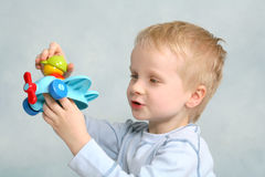 Boy Plays with Toy Plane. Small male tot plays with a colorful plastic toy airplane.  Child is holding plane up in front of his face and his gaze is focused on Royalty Free Stock Image