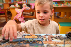 Boy plays with toy railroad stock photo