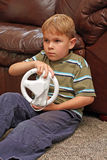 Boy plays video game. A 6-year-old boy sits on the carpet  holding a game controller and plays a popular video game Royalty Free Stock Image
