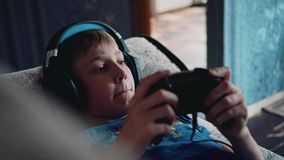 The boy plays a video game lying on the couch with a headset on his head. Close-up enough. Multimedia entertainment. Development and training stock footage
