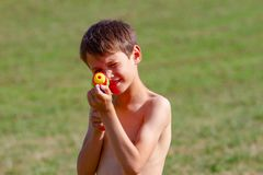 Child plays with a water gun. Boy plays with a water gun toy outdoors stock photos