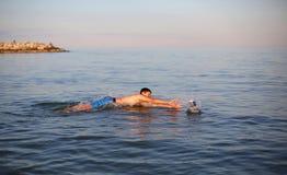 Boy plays water polo in the sea Stock Photos