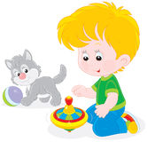 Boy plays with a whirligig and kitten. Little boy playing with a grey kitten and a humming-top Royalty Free Stock Photos