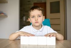 Boy plays with white cubes. Place for your text . Stock Photography