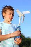 Boy plays with wind-driven generator. The little boy against the blue sky plays with a wind-driven generator stock photos