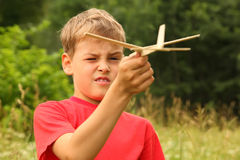 Boy plays with wooden airplane on nature Stock Photos