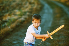 A boy plays with a wooden sword Stock Photo