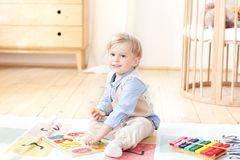 The boy plays with wooden toys and numbers. Educational wooden toys for the child. Portrait of a boy sitting on the floor in the c royalty free stock image