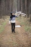A boy plays in the woods with a toy plane. autumn games in the w stock images