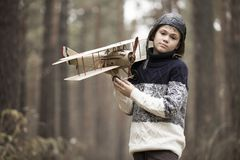 A boy plays in the woods with a toy plane. autumn games in the w stock photos