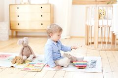 The boy plays xylophone at home. Cute smiling positive boy playing with a toy musical instrument xylophone in the children`s white stock photography