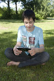 Boy with Playstation. Boy playing Playstation console outdoors Stock Image