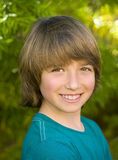 Boy with Pleasant Smile. A head shot of a happy boy with brown hair and eyes, in a blue t-shirt, with a pleasing, pleasant smile standing in a backyard garden Royalty Free Stock Photos